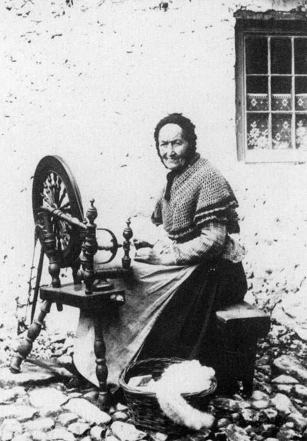 Old photograph of a crofter with her spinning wheel on the Island of Mull, Inner Hebrides, Scotland