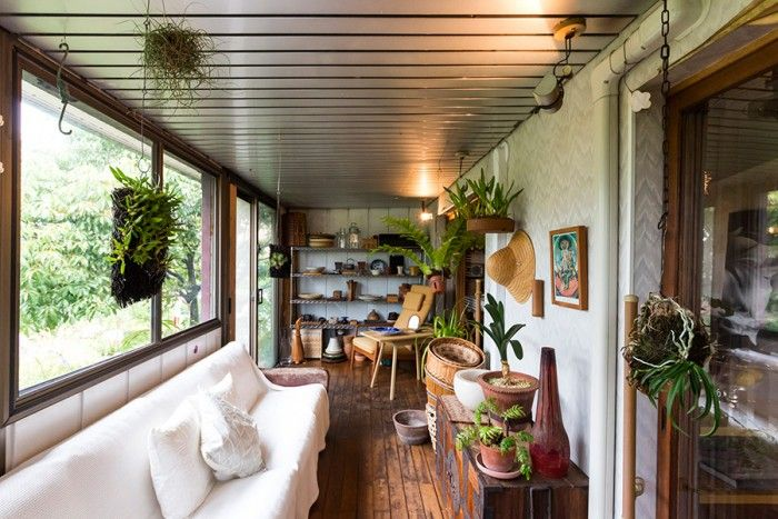 古い家具や雑貨、アート、植物が融合したサンルーム。庭に面し、穏やかなムードが流れている。