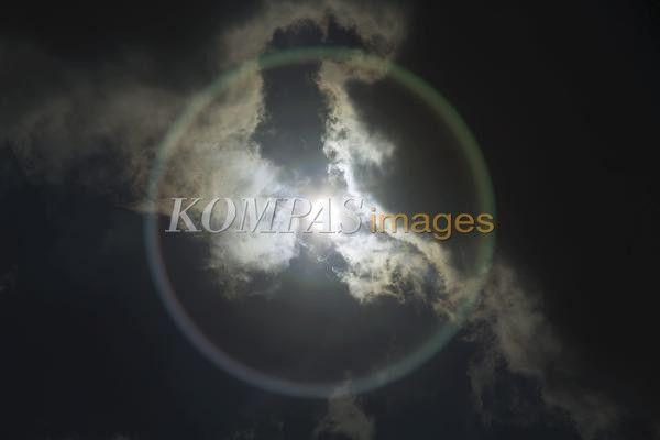 Fenomena halo matahari di langit Jakarta, Senin (14/4/2014). Fenomena alam ini terjadi saat kelembaban cukup tinggi di sekitar atmosfer. Kelembaban mengakibatkan efek cahaya matahari terpantul melalui prisma air di awan, sehingga membentuk semacam lingkaran pelangi di langit. Cincin pelangi dalam astronomi disebut halo, biasanya terjadi saat awan berjenis cirrus atau awan tipis yang tinggi.