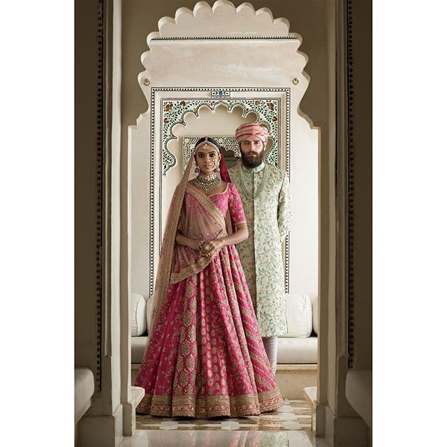 Bridal Wear - Sabyasachi Pink Bridal Lehenga with Gold Dull Embroidery | WedMeGood | Groom in a Mint Green Sherwani with a Tie and Die Pink Safa #wedmegood #indianbride #indiangroom #indianwedding #sabyasachi #pink #lehenga #sherwani #safa #green #coupleshot