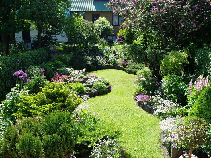 Beautifully designed small garden with deep beds full of rich plants of varied heights.