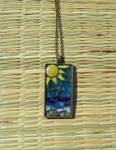 A Day at the Beach~  This shimmering glass mosaic pendant necklace transcends the beauty of the beach and ocean with shiny aqua, blues, sunny yellow and caramel hand-cut glass. The center of the sun is a glass coin bead. The pendant features a 24x47mm (0.94 inches x 1.85 inches) rectangular antique bronze bezel hung on an 18 inch antique bronze chain. Black grout is used to set the design and frame each shiny mosaic glass piece; finished with a sealant for protection. Please note that there…