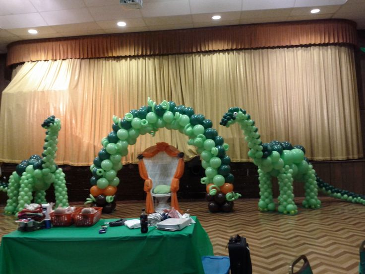 Dinosaur balloon sculpture for baby shower party decoration with balloon arch and wicker chair http://www.dreamarkevents.com/index.html