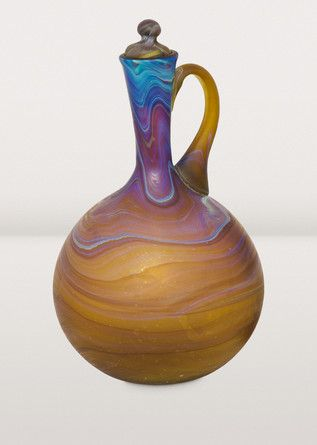 A colorful recycled glass carafe hand-blown by artisans of Hebron Glass & Ceramic Factory. In Phoenician glass blowing, artisans add substances to the molten glass, with the resulting reaction creating a range of colors. Working with this process takes an especially skilled hand, and is reserved for the true masters of the art. Each piece has its own unique blend of color and pattern.