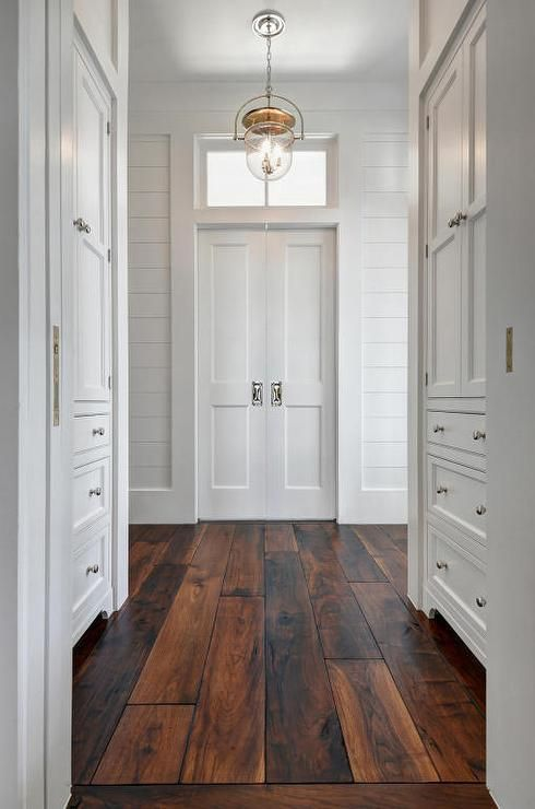 Beautiful barn wood floors illuminated by an Urban Electric Dover bell light while walls lined with inset, built in white shaker cabinets fitted with polished nickel knobs lead to white bi-fold doors positioned under a small transom window flanked by white shiplap walls.