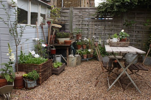 pebbles, table and lots of plants give life to a garden corner