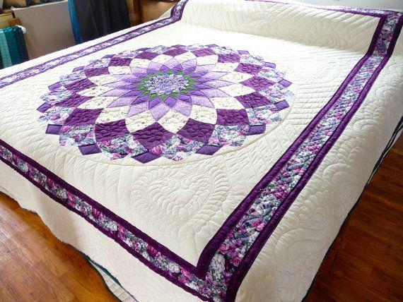 Hermosa Dahlia flota en medio de un fondo blanco fuertemente acolchado. Una mezcla de sólidos y patrones componen la Dalia. Los colores incluyen violetas y lavandas. Frontera y vinculantes son en telas contrastantes. Dimensiones aproximadas: 95 X 111    Si te gusta los colores y el patrón de esta colcha, revisa nuestro edredón Amish Country uvas aquí: https://www.etsy.com/listing/120020189/amish-county-grapes-quilt?ref=shop_home_active    Cada edredón Amish espíritu es mano acolchada por un…