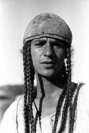 Portrait of a young Yazidi man with plaited hair, wearing a distinctive hat. 1951, Jabal Sinjar