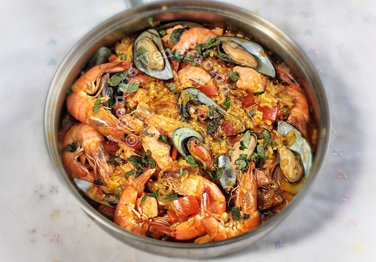 In this recipe for seafood arroz a la Valenciana, the rice is accompanied by shrimps, mussels and salmon. The rice was colored with turmeric and paprika.
