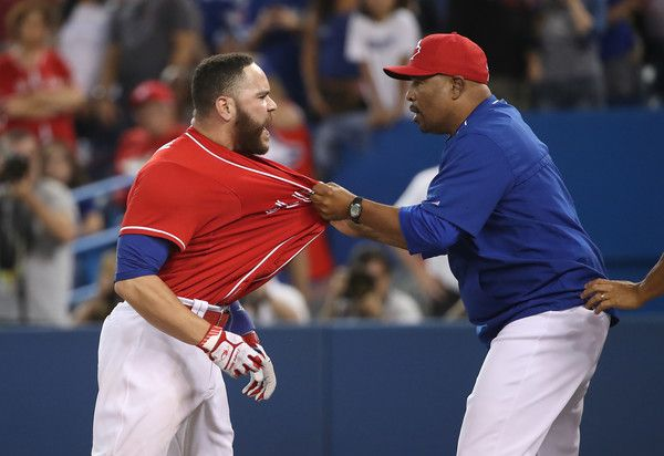 Russell Martin #55 of the Toronto Blue Jays is restrained acting manager DeMarlo Hale #16 after being ejected for arguing a called third strike by home plate umpire Vic Carapazza #19 in the thirteenth inning during MLB game action against the Cleveland Indians on July 1, 2016 at Rogers Centre in Toronto, Ontario, Canada.