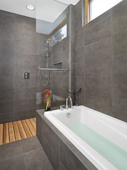A charcoal tile bathroom with cedar wood for the shower floor. The wood slats sit above tile and can easily be removed to clean beneath.