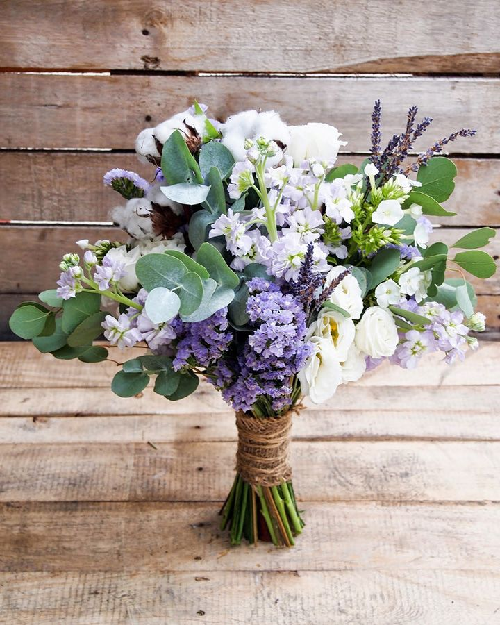Purple and white bouquet wrapped with burlap