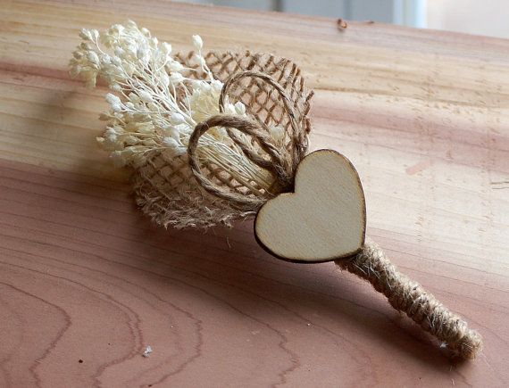 This boutonniere is a small bunch of dried babys breath and jute twine loops wrapped up in burlap and jute twine. Finished off with a wooden heart. Wooden heart edges have been wood burnt to give it more rustic character. All to create a rustic yet beautiful boutonniere with lots of charm.  The babys breath has a slight off white/ivory color to it. Perfect for a vintage, rustic, outdoor or country wedding. This boutonniere measures approximately 4 tall by 1 3/4- 2 wide making it the...