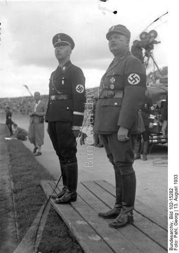 [Appell der SS-Gruppe Ost am 13.8.33 im Deutschen Stadion in Berlin-Grunewald] Der Reichsführer der SS. Himmler (links) und der Stabschef der S.A. und SS. Hauptmann Röhm.  Der Stabschef der SA. Ernst Röhm, wurde auf Vorschlag des Reichskanzlers zum Reichsminister ohne Geschäftsbereich ernannt! Der [vom] Reichspräsidenten zum Reichsminister ernannte Stabschef der SA. Ernst Röhm, welcher somit Mitglied der Reichsregierung wurde.