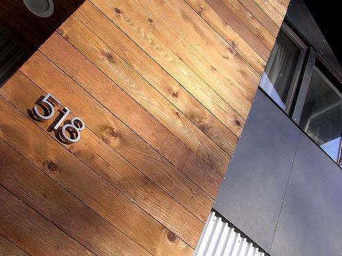 A modern makeover for the exterior of this house included cedar-planked support beams, eco-friendly fiber cement siding, and house numbers in classy Neutraface.