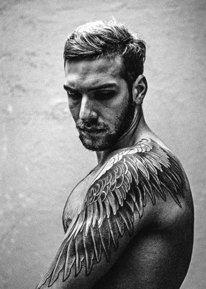 tätowierter mann mit einem großen schwarzen tattoo idee für einen tollen schwarzen engelsflügel tattoo, die den männern sehr gut gefallen könnte