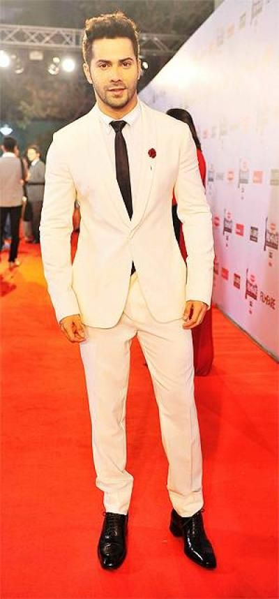 This hot guy of Bollywood certainly knows how to play it cool. Varun Dhawan was seen in a white Emporio Armani suit teamed up with a slim tie and black Tom Ford shoes. And, that small red lapel pin truly added a dash of excitement in his monochrome look. - bollywoodshaadis.com