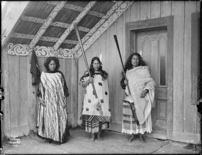 Three unidentified Maori women from Ngai Tuhoe with cloaks and taiaha