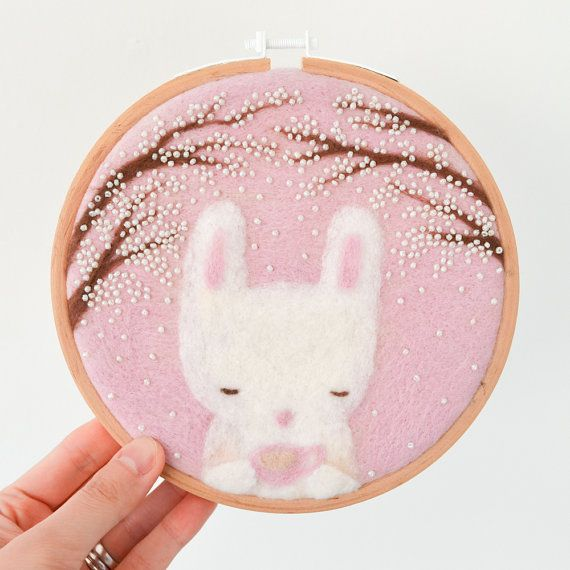 Invito questo piccolo coniglietto a prendere il tè con voi! Questo ago infeltrito, grazioso coniglietto è pronto per ravvivare il vostro camera. È incorniciato in un cerchio in legno di alta qualità e rifinito con tessuto della protezione sul lato opposto. Sarà un bel regalo per la casa di un amante degli animali o un vivaio.  :: Dimensioni:: 6 a / 15cm di diametro  :: Materiali:: Telaio da ricamo in legno Tessuto di lana tessuta Feltro di lana (da Australia e Nuova Zelanda) Branelli del…
