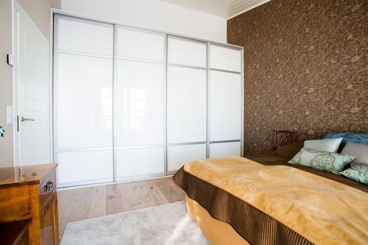 Huonekorkeus kannattaa hyödyntää säilytyksessä. Korkean makuutilan liukuovikomerossa vaatteet mahtuvat roikkumaan tangolla kahdessa tasossa. - Unique Home