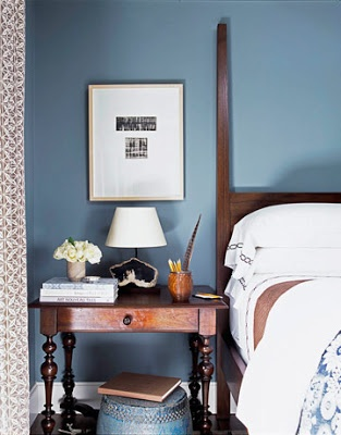 A masculine blue painted wall balances out a traditional wood night stand and wood four poster bed