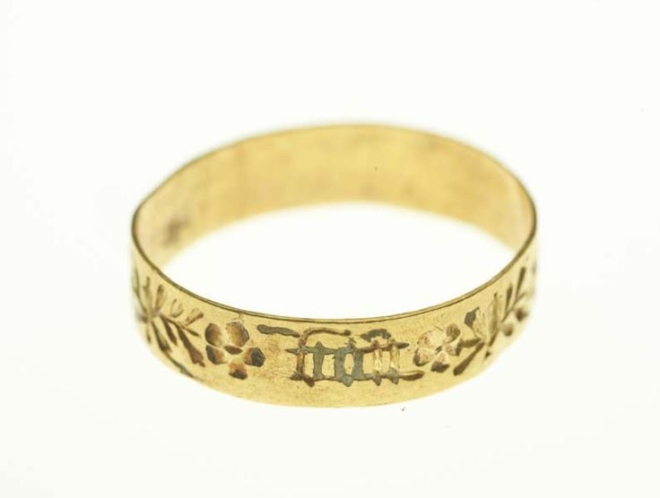 Posy ring A gold posy ring of flat section, engraved externally with flowers and leaves (retaining traces of white and red enamel) and inscribed in black letter 'en bon an' ('a good year'). There are no marks.  Production Date: Late Medieval; 15th century Measurements: DM 17 mm; WT 1.1 g Materials: gold; enamel