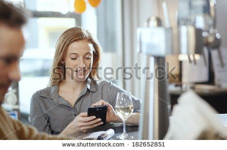 beautiful young woman using her smartphone in a bar - stock photo