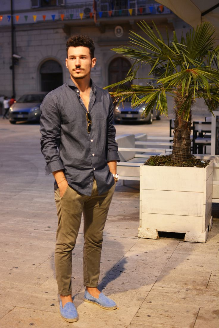 Shop this look on Lookastic:  https://lookastic.com/men/looks/charcoal-long-sleeve-shirt-brown-chinos-blue-espadrilles-brown-sunglasses/4990  — Blue Canvas Espadrilles  — Brown Chinos  — Charcoal Long Sleeve Shirt  — Brown Sunglasses