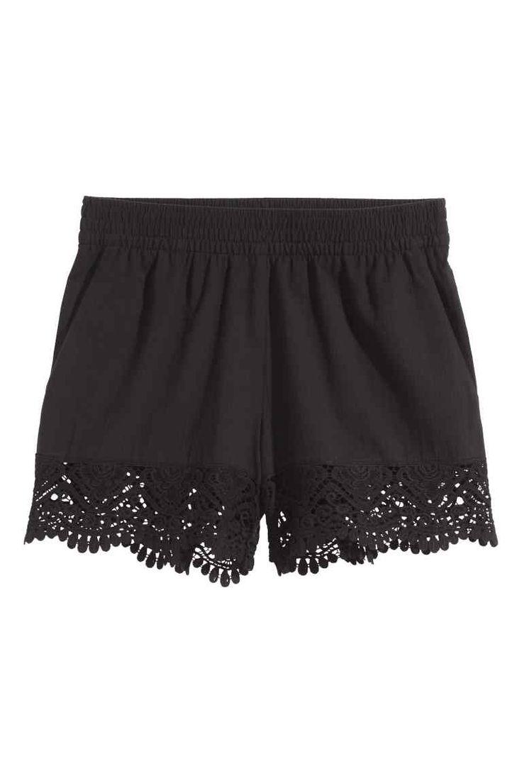 Calções em algodão com renda: Calções em tecido de algodão com pernas largas, elástico na cintura e bolsos laterais. Barra larga de renda no remate das pernas.