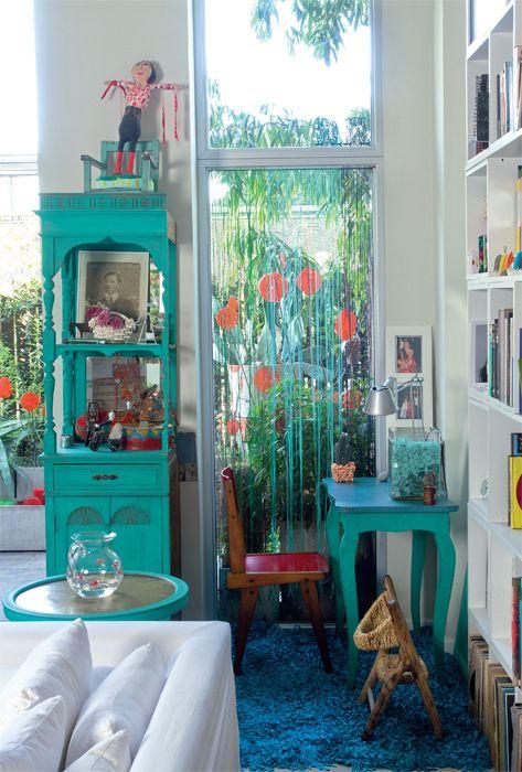 El color aguamarina invade este rincón junto a la ventana. El paño fijo de vidrio que se alarga verticalmente se cubrió con unas cintas bebé que hacen las veces de sutiles cortinas. El escritorio, la silla y el mueble vajillero pertenecieron a la casa de la abuela de la paisajista. Ella los recicló y pintó. La alfombra azul procede de la ambientación para una Casa FOA y el banquito, de un viaje a Uruguay.