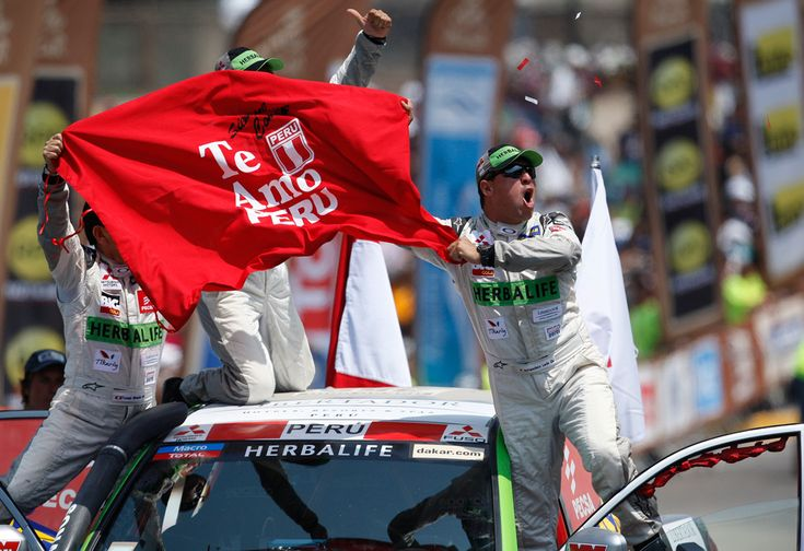 "Mitsubishi driver Francisco Leon, right, of Peru, waves a banner that reads in Spanish ""I love you Peru"" during the symbolic start of the Peru-Argentina-Chile Dakar Rally in Lima, Peru, on Jan. 5, 2013. The race of over 400 vehicles including cars, bikes, trucks and quads begins Saturday in Lima and finishes in Santiago, Chile on Jan. 20. (Karel Navarro/Associated Press) #"