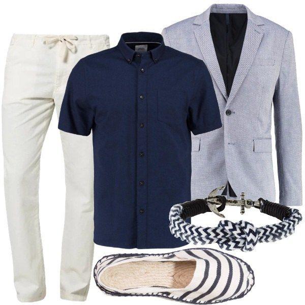 Giacca di cotone, nella nuance del blu, con due bottoni a chiusura e tasche con patta, camicia navy di cotone, pantaloni in misto lino, con laccio in vita e cerniera nascosta. Le scarpe sono delle espadrillas, in fantasia a righe, bracciale in metallo e cotone, con dettaglio ancora. Se preferite un look più sportivo, consigliamo un cardigan o un giubbino leggero.