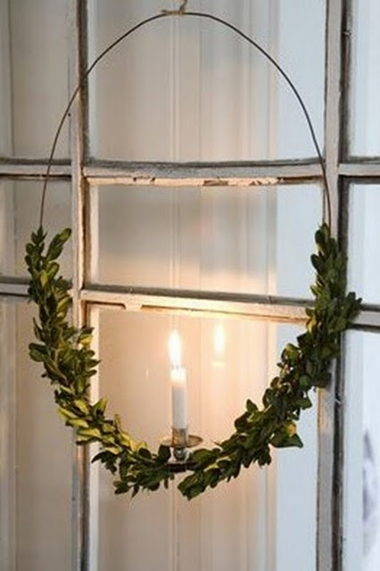 I've always loved a single candle in each window as elegant holiday lighting; I LOVE the small swag of boxwood.