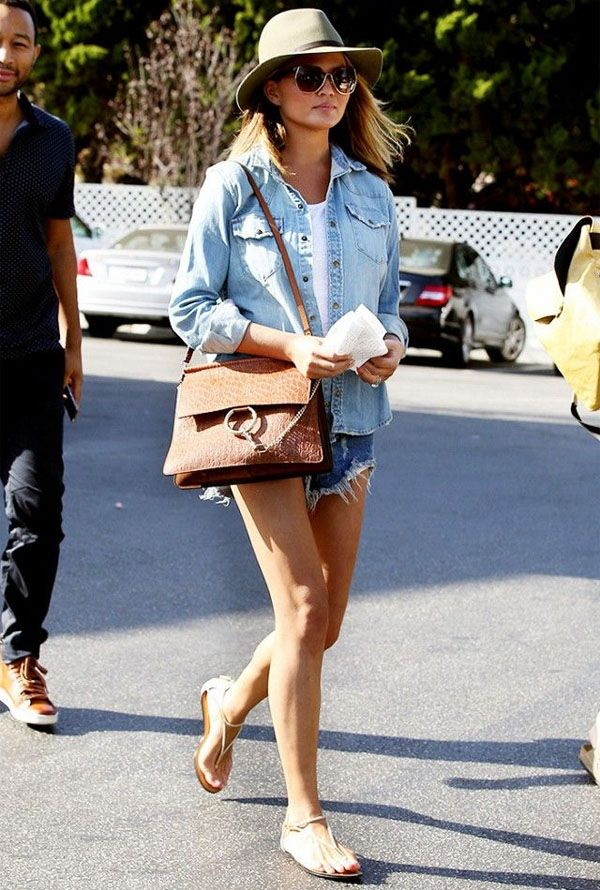 Street style de Chrissy Teigen com look todo denim e chapéu no verão.
