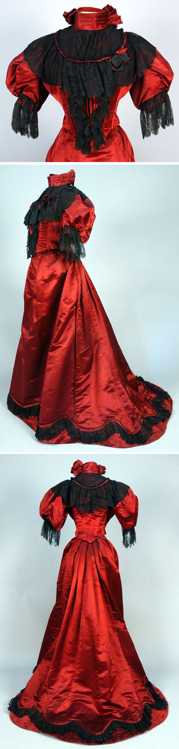 Dress ca. 1890. Two-piece garnet silk with high, boned-neck bodice with short puffed sleeve and black lace trim. Sheer neckline, trained skirt with piped serpentine hem band and black ruffled lace. Underside of train backed in stiffened gauze with pleated ruffles. Whitaker Auctions