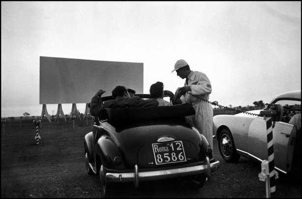 ITALY—An attendant handing out a loudspeaker to customers of the drive-in, near Rome, 1956. Today's Pictures: Two Thumbs Up