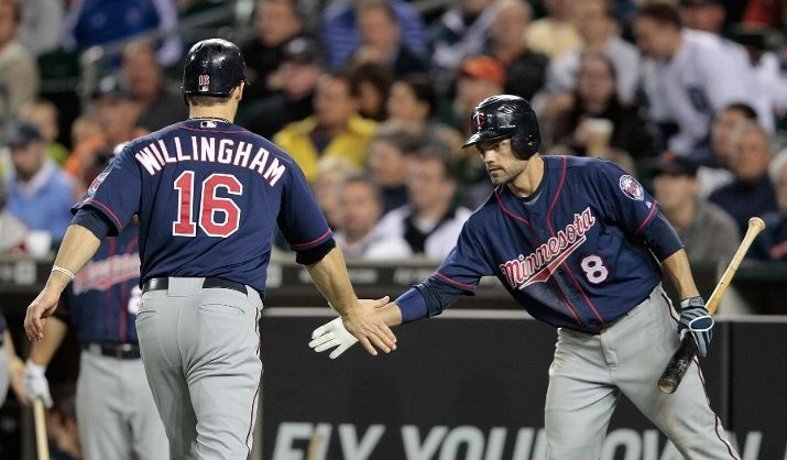 Josh Willingham #16 of the Minnesota Twins scores on a single to right field by Alexi Casilla #12 and is congratulated by teammate Jamey Carroll #8 in the sixth inning during the game against the Detroit Tigers at Comerica Park on May 16, 2012