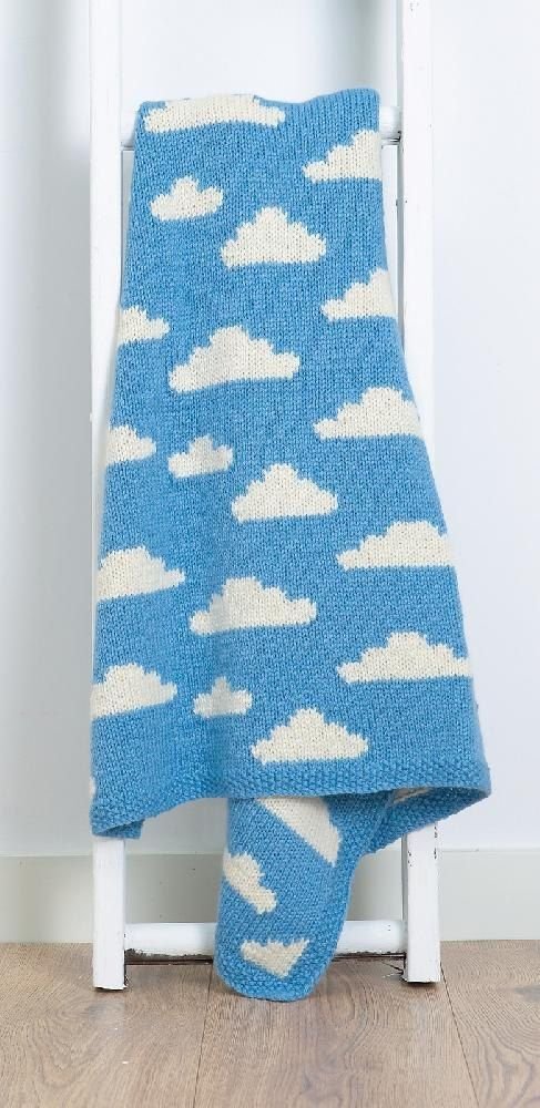You'll be on cloud nine with this soft and cosy blanket, featuring fluffy little clouds in a blue summer sky.Fluffy White Clouds is a baby blanket inspired by those perfect spring days where the clouds drift through the sky.The blanket is knitted in stocking stitch using the intarsia technique to incorporate the clouds. The blanket measures 90.5 × 67 cm (35.5 × 26.5 in), sized to fit a pram, crib, cot or Moses basket, with a 2.5 cm (1 in) moss stitch border to prevent curling. The border is…