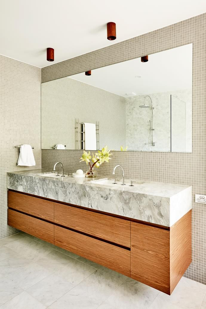 """This ensuite by Studio Gorman evokes the glamour of a New York hotel room with cloudy greys and glowing timbers. """"The brief for the main ensuite was to create the ambience of a New York luxury hotel – bold, generous and robust yet delicate. To achieve this we were meticulous in space planning, considering the proportions of each key element to create a generous shower and vanity with plentiful storage,"""" says designer Suzanne Gorman."""