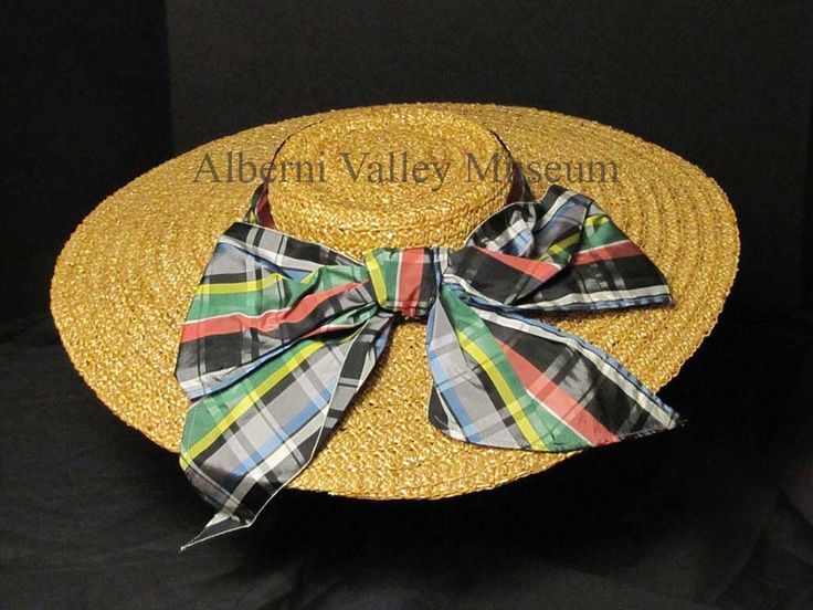 "Straw hat with a shallow ""pork pie"" crown and plaid taffeta ribbon that belonged to Nellie Fisk (nee Bourne).  During the inter-war years (1920s-1930s), accessories were an integral part of a woman's wardrobe.  Summer hats, especially during the 1930s, were large, wide-brimmed and trimmed with such things as flowers, ribbons and osprey feathers.  [Alberni Valley Museum Collection 1978.22.5]"