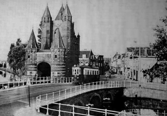 Spaarnewoudestraat Haarlem (jaartal: 1930 tot 1940) - Foto's SERC  Haarlem (1938) Amsterdamse poort met blauwe tram, en doorlopend water. Met op de achtergrond de Spaarnewoudestraat.