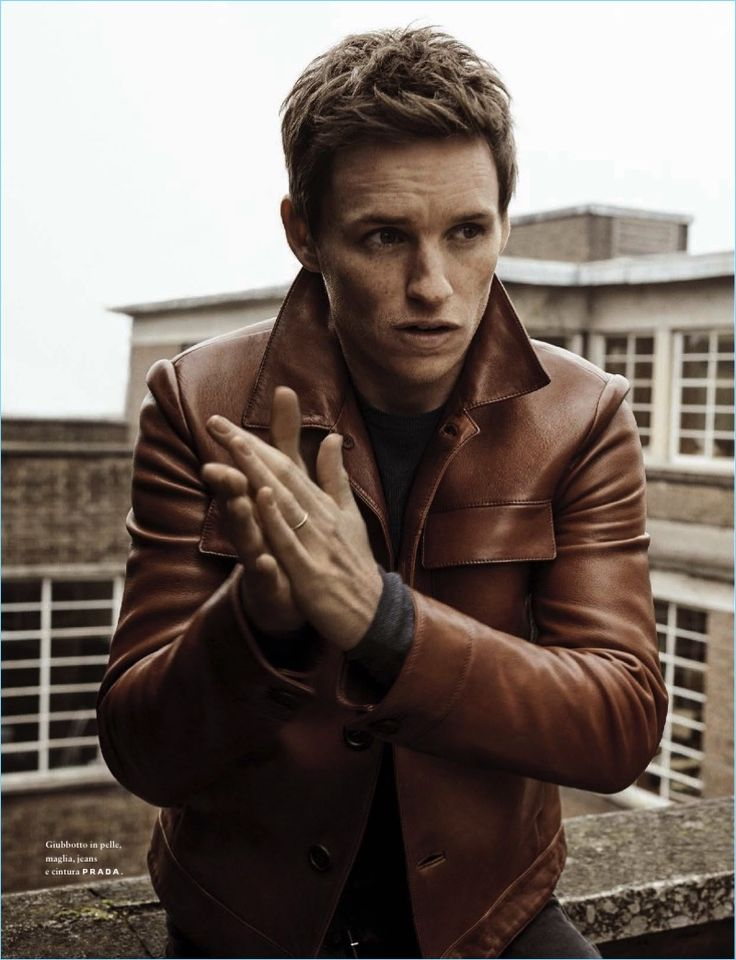 Clad in Prada, Eddie Redmayne wears a brown leather jacket, sweater, and denim jeans.