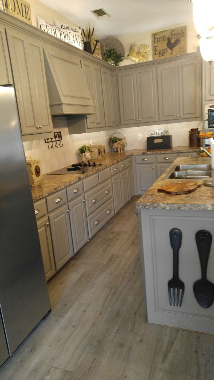Kitchen cabinets painted with Reclaim Beyond Paint in Pebble. Cerim Elite Gray Porcelain Tile 6X36 #farmhousekitchen #Reclaimbeyondpaint #CerimEliteGrayPorcelaintile
