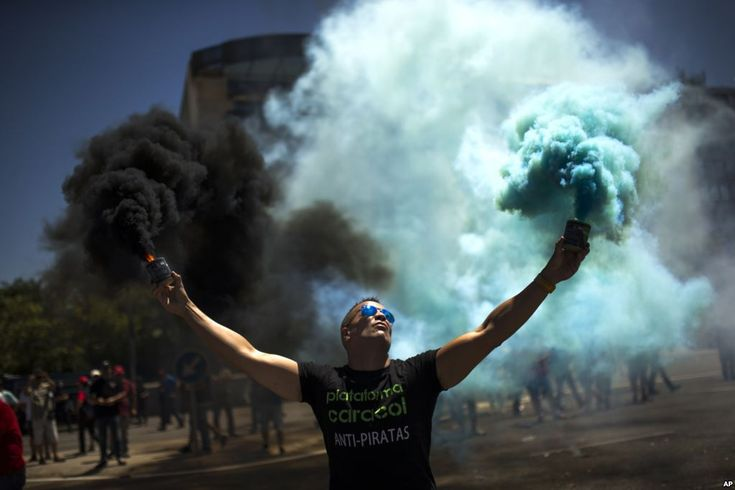 July 27, 2017:  A man holds smoke bombs during a protest by Spanish taxi drivers unions in Madrid. They called for a 24-hour strike to protest the increase in cars run by private companies offering cheaper, mobile ride-hailing services..