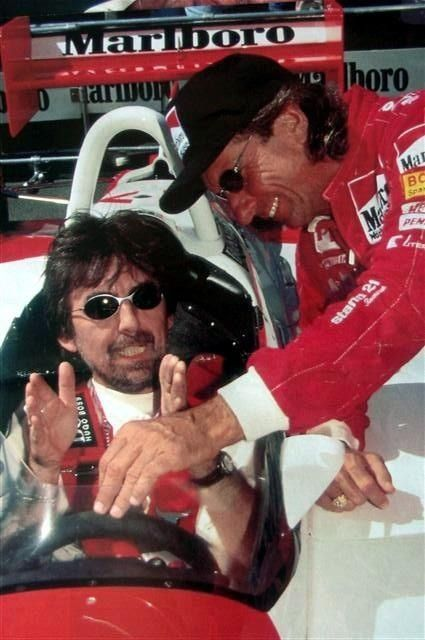 George Harrison gently explains to Emerson Fittipaldi how to make a F1 McLaren weeps.