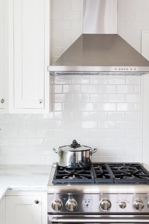 Beautiful white kitchen features a stainless steel hood mounted to an all white subway tile backsplash beside white shaker upper cabinets and above a stainless steel oven range positioned next to white lower cabinets adorning polished nickel knobs and a honed white marble countertop.