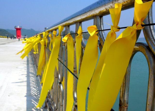 沈没現場近くの港では、防波堤の柵に結ばれた黄色いリボンが風にはためいていた=韓国南西部・珍島、広島敦史撮影 ▼24Apr2014朝日新聞|生きて帰れと黄色いリボン 韓国、沈没事故後に広がる http://t.asahi.com/ekb5 #Sewol #Yellowribbons