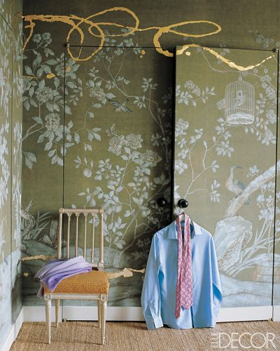Decorator Jeffrey Bilhuber chose a hand-painted de Gournay wallpaper with a garden motif for the closet doors and walls of his Manhattan bedroom, and then commissioned artist Nancy Lorenz to add painterly flourishes in gold leaf on resin. The 18th-century French chair has an ­ostrich-covered seat.    Photographer: William Waldron