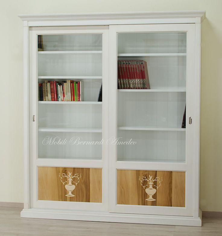 Libreria con ante scorrevoli, finitura bianco poco anticato, vetri molati e pannelli in noce intarsiato.