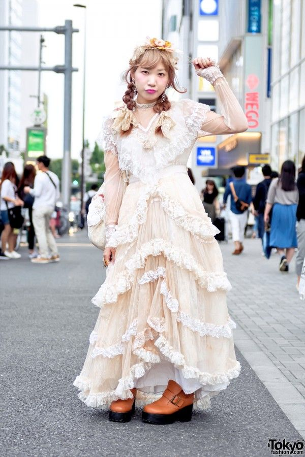 Tyatyamal is wearing a long vintage ruffle dress from the Tokyo vintage shop Meno with Comyu platforms and a bag by the indie Japanese handmade fashion brand Freckleat. Her accessories – which include a vintage headpiece, costume jewelry earrings, a cameo necklace, and several ring – came from Too Much and Ruka.